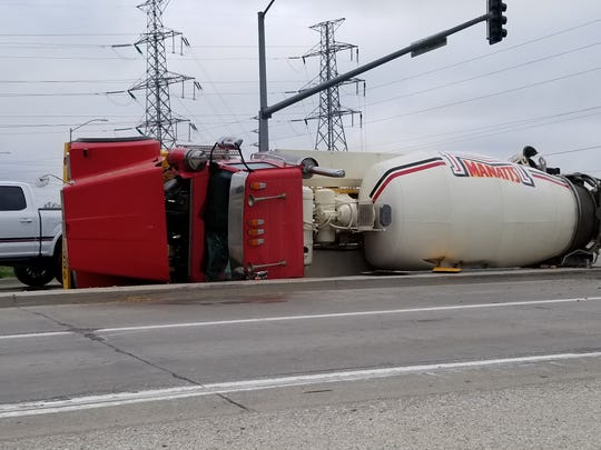 A semi-truck lays on its side at the intersection of NW Beaver Drive and NW  Johnston Drive.
