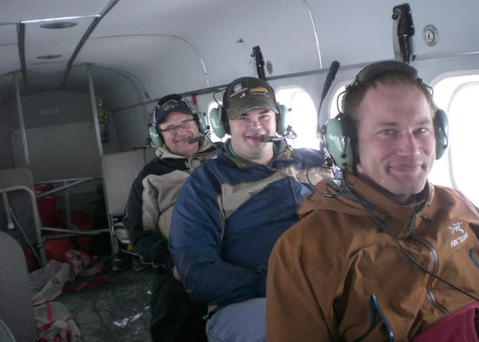 Dave Mortensen, left, and his son Ethan, middle, ride in an airplane in Alaska while visiting Ethan's brother, Jacob, shown right. Dave and Ethan died April 14 when their car was struck by a train in Cedar Rapids.