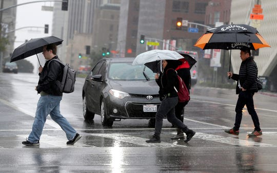 In this Monday, Feb. 6, 2017 file photo, pedestrians cross a rainy street in downtown Los Angeles.