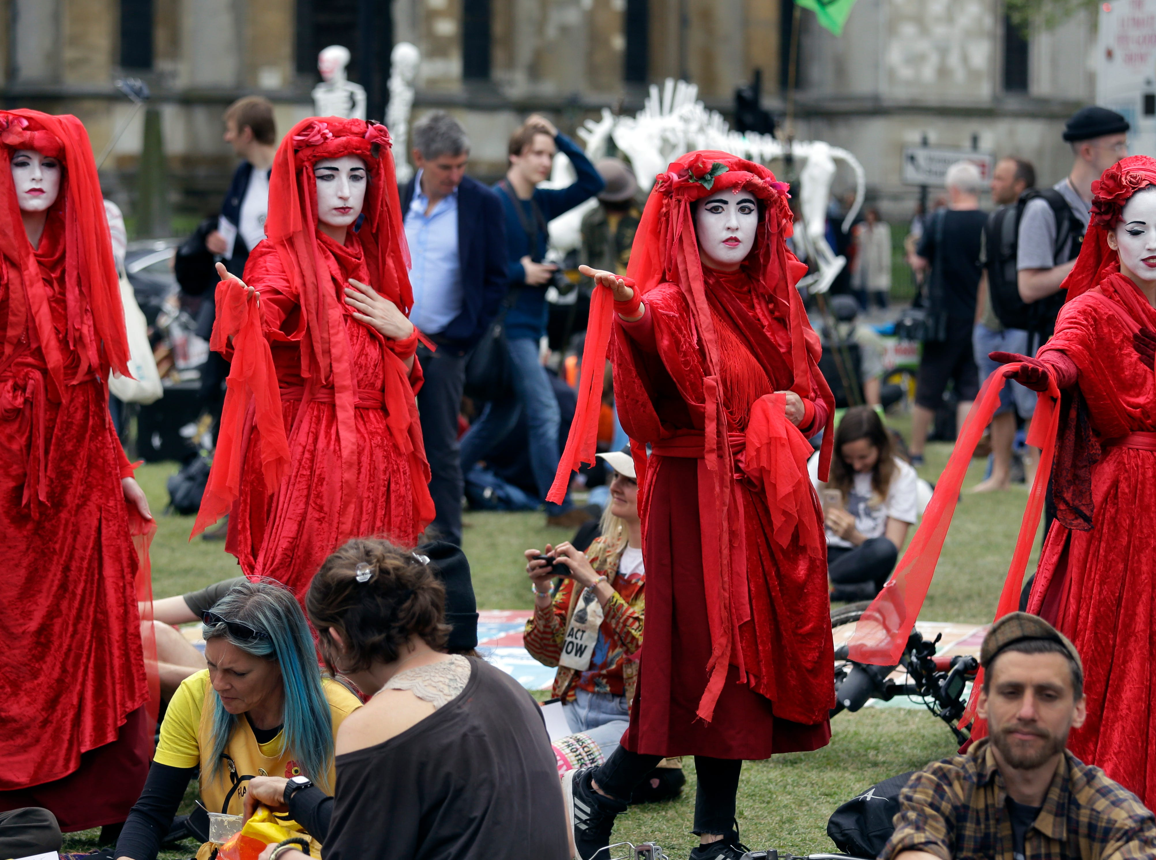 Members of the so-called 'Red Brigade' attend a climate protest in Parliament Square, in London, Tuesday April 23, 2019. The non-violent protest group, Extinction Rebellion, is seeking negotiations with the government on its demand to make slowing climate change a top priority.