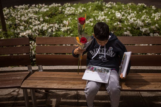 A boy hold roses as he reads a book after buying it at a makeshift stand as Catalans celebrate the day of their patron saint in Barcelona, Spain, Tuesday, April 23, 2019. Sant Jordi, or Saint George in English, is one of the most important holidays in Catalan culture. To mark the date, lovers close friends and family traditionally gift each other with a red rose and a book. (AP Photo/Emilio Morenatti)