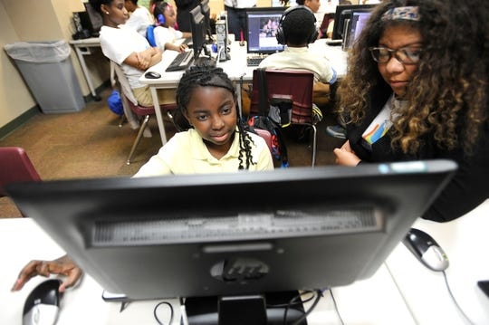 Flagship Academy third grader Shantinique Brown, 8, reads Hansel and Gretel with seventh grader Rebecca Murray, 13, during the school's after school program. Middle school students at Flagship Academy charter school in Detroit are participating in Teen Trendsetters, a mentoring program.