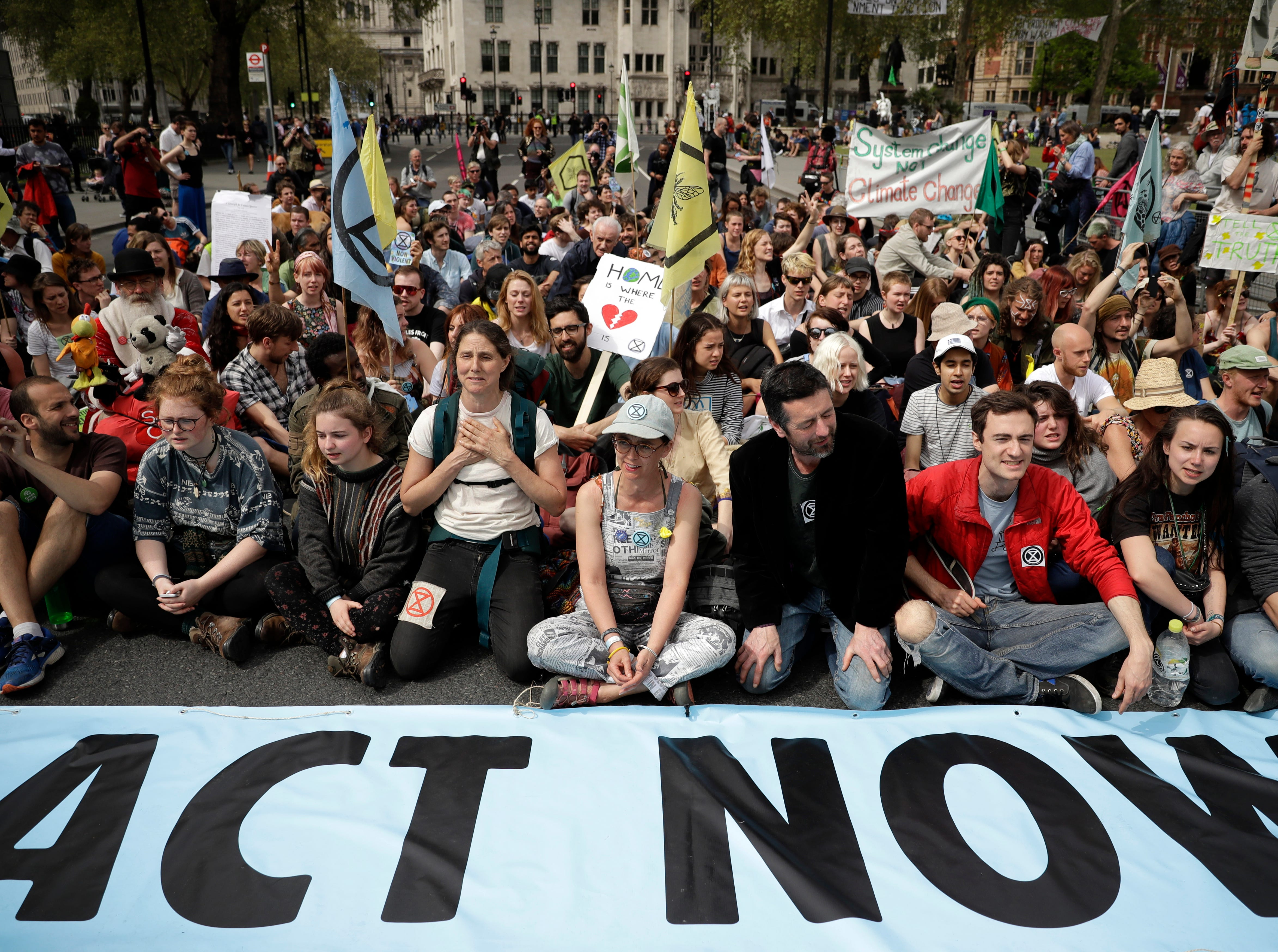 Protesters sit in the road in Parliament Square, in London, Tuesday April 23, 2019, during a climate protest. The non-violent protest group, Extinction Rebellion, is seeking negotiations with the government on its demand to make slowing climate change a top priority.