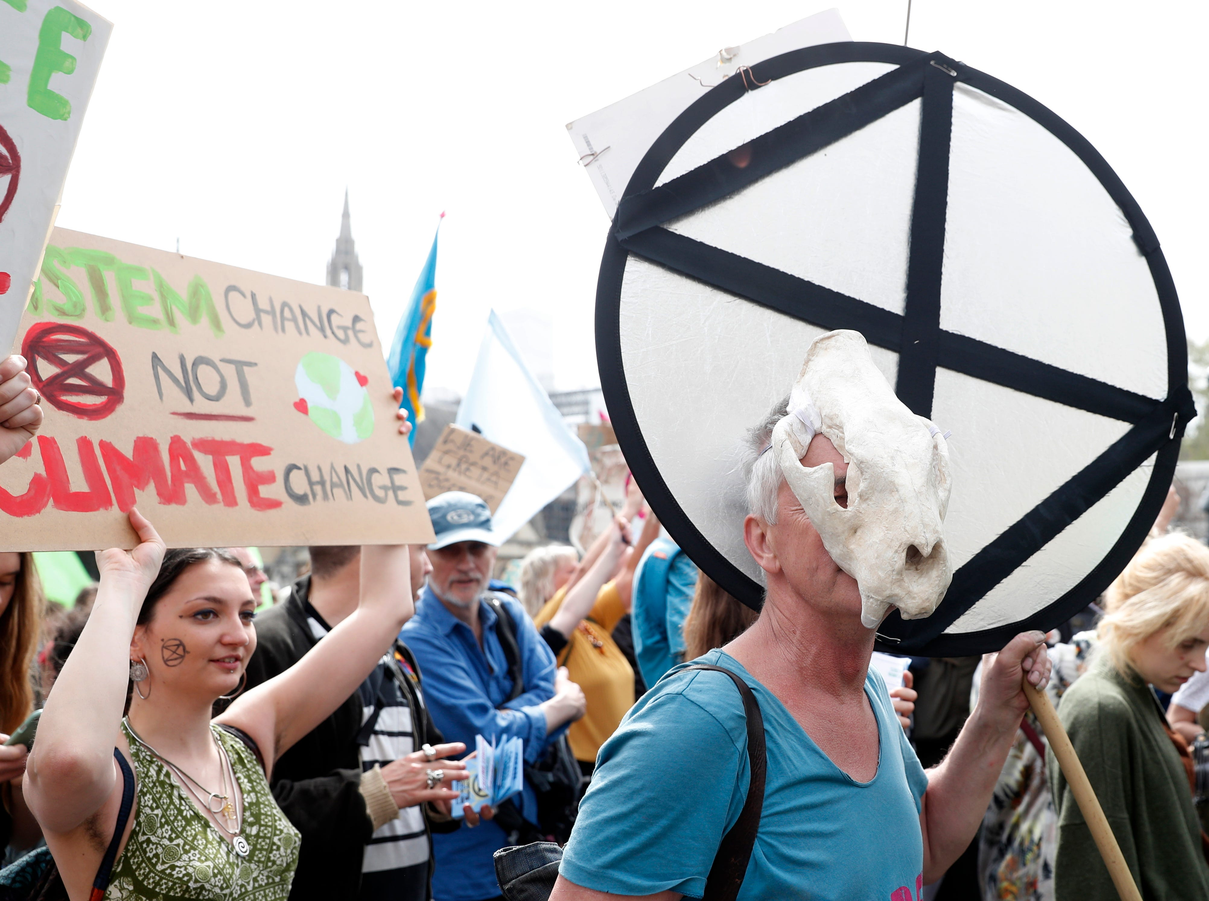 A protester wearing an animal mask arrives with others in Parliament Square, in London, Tuesday April 23, 2019, during a climate protest. The non-violent protest group, Extinction Rebellion, is seeking negotiations with the government on its demand to make slowing climate change a top priority.