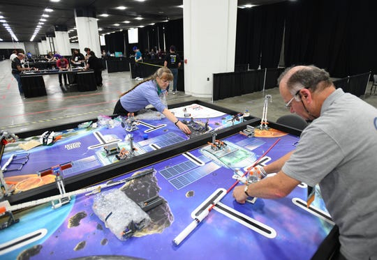 Volunteers Yosi Karl from Israel and Andrea Tanner from the United Kingdom set up a robotic playing area at Cobo Center in Detroit on Tuesday.