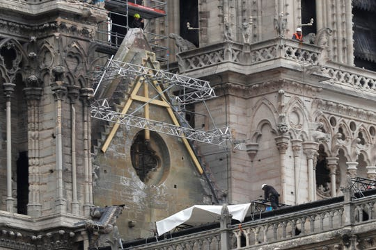 Workers install tarps at Notre Dame cathedral,Tuesday, April 23, 2019 in Paris.
