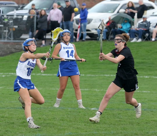 Avery Snyder of Horseheads passes the ball in front of Elmira's Calli Overton during girls  lacrosse action April 23, 2019 at Horseheads High School.