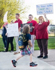 """Tekoppel Elementary teachers Bryan Norman, left, Michelle Adams-Smith, center, and Virginia Marcee, right, hold up signs as a student walks past while participating in Indiana's """"Red for Ed"""" Teacher Walk-in Tuesday, April 23, 2019. Teachers across Indiana participated in the walk-in to send a message to state legislators."""