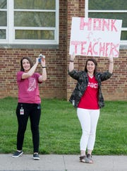 """Tekoppel Elementary teachers Ellen Timmons, left, honks a bike horn while Kaci Grambrel, right, holds up a sign in front of their school while participating in Indiana's """"Red for Ed"""" Teacher Walk-in Tuesday, April 23, 2019. Teachers across Indiana participated in the walk-in to send a message to state legislators."""
