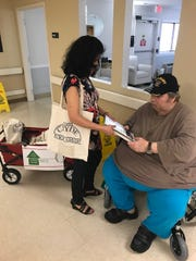 Nelcy Elder handis a book to a veteran, Dale Gordon, at Heritage Village of Clyde care center.