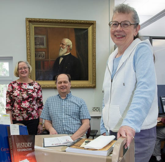 John Ransom, center, has been promoted to head librarian at the Hayes Presidential Library. Librarians Pat Breno, left, and Sharon Barnett work with him in the library.