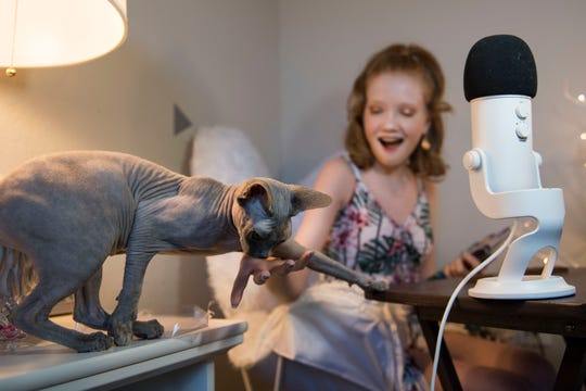 "13-year-old ASMR YouTube personality Makenna Kelly is interrupted by her one-year-old sphynx cat Gwen while filming a video for her YouTube channel ""Life with MaK"" on Friday, April 19, 2019, at her home in Fort Collins, Colo."