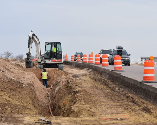 Construction crews work on what will become an additional lane to Harmony Road in north Windsor on April 16.