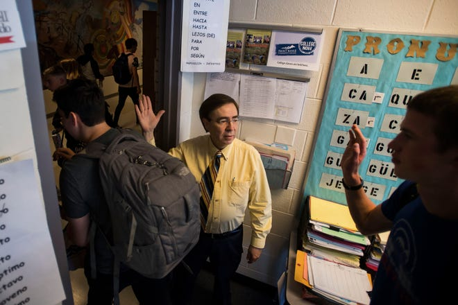 Spanish teacher Tony Espinoza gives his students high-fives as they leave class on Tuesday, April 23, 2019, at Poudre High School in Fort Collins, Colo.