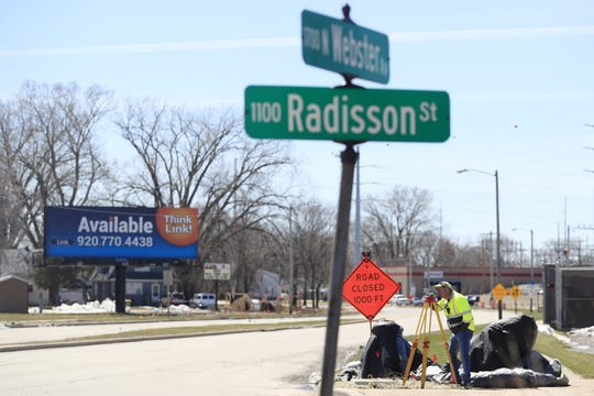 City surveyors work on Webster Avenue in preparation for the road's reconstruction this summer.