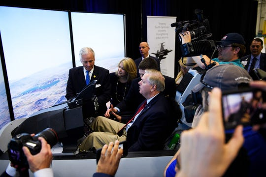 Sen. Lindsey Graham tries out an F-16 simulator during a ribbon cutting ceremony for the fighter jet's production line at Lockheed Martin Tuesday, April 23, 2019.