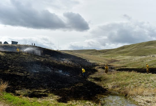 A volunteer firefighters respond to a grass fire on Cove Lane, Tuesday afternoon.
