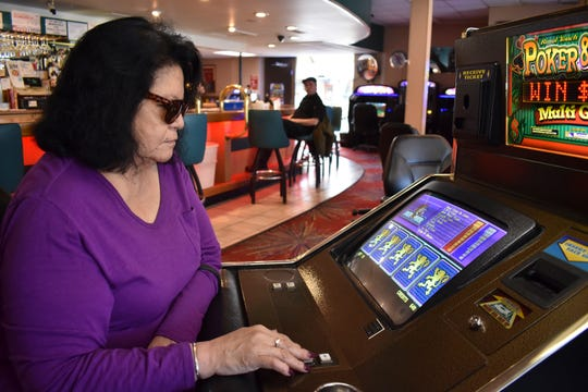Lucille Brien plays a video poker machine at the Monte Bar and Casino in Billings, Montana, Tuesday, April 23, 2019. Montana, Iowa and Indiana are poised to be the first states to legalize sports betting this year, almost a year after the U.S. Supreme Court ended Nevada's monopoly. (AP Photo/Matthew Brown)