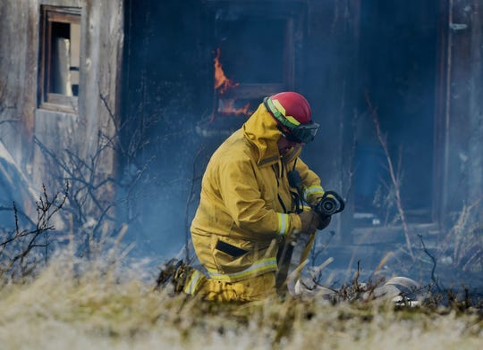 A volunteer firefighter sets up a hose while responding to a grass fire on Cove Lane, Tuesday afternoon.