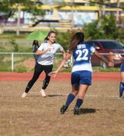 Academy's Mia San Nicolas pursues the ball against Harvest player Leandra Loftis (22) during a IIAAG Girls Soccer match against the Harvest Eagles at the George Washington High School Field in Mangilao, April 22, 2019. San Nicolas has been a bright spot in Academy's 7-1 season thus far.