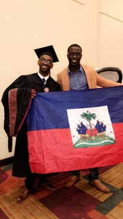 Johnson Simon (left) and brother Johnnie Simon held up the flag of Haiti after Johnson graduated with a master's degree from the Herron School of Art and Design.