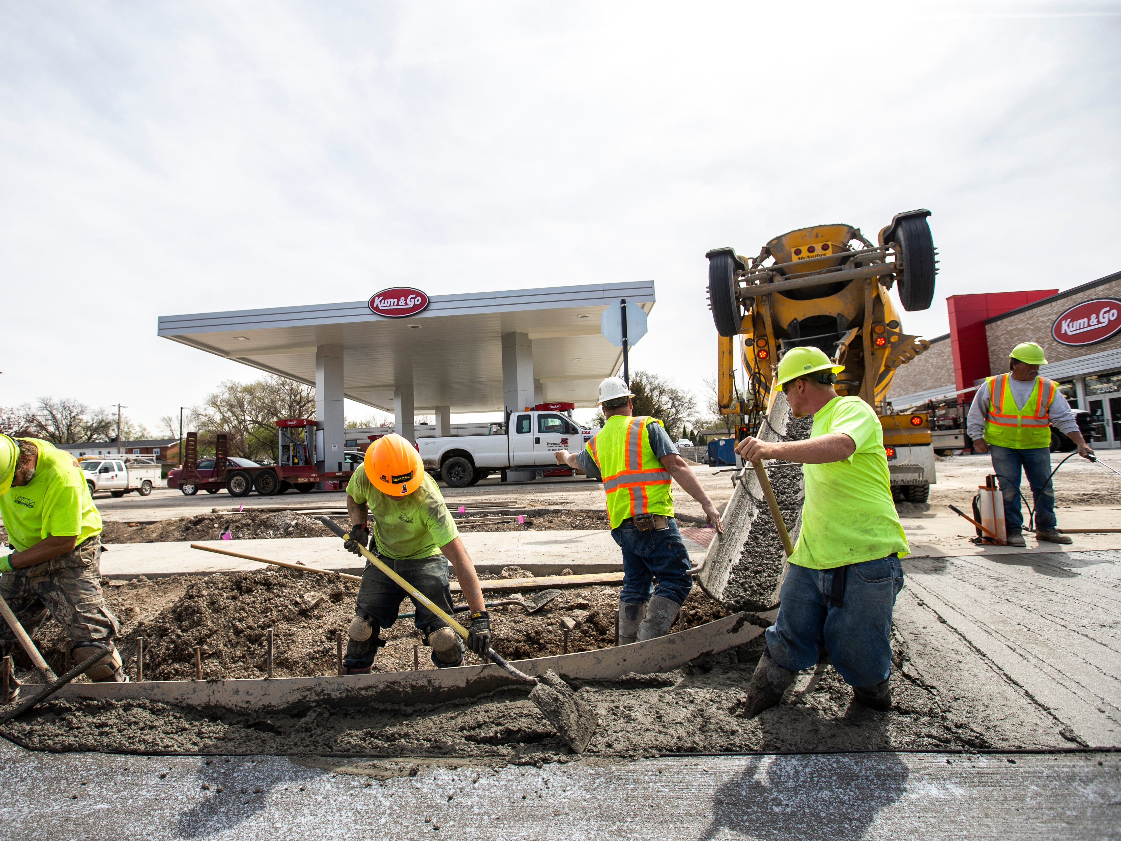 Bud Maas Concrete foreman Steve Conley, center right, gives instructions while concrete gets poured for an entrance off of Muscatine Avenue as construction nears competition, Tuesday, April 23, 2019, at a new Kum & Go location on the corner of Muscatine and First Avenues on the east side of Iowa City, Iowa.