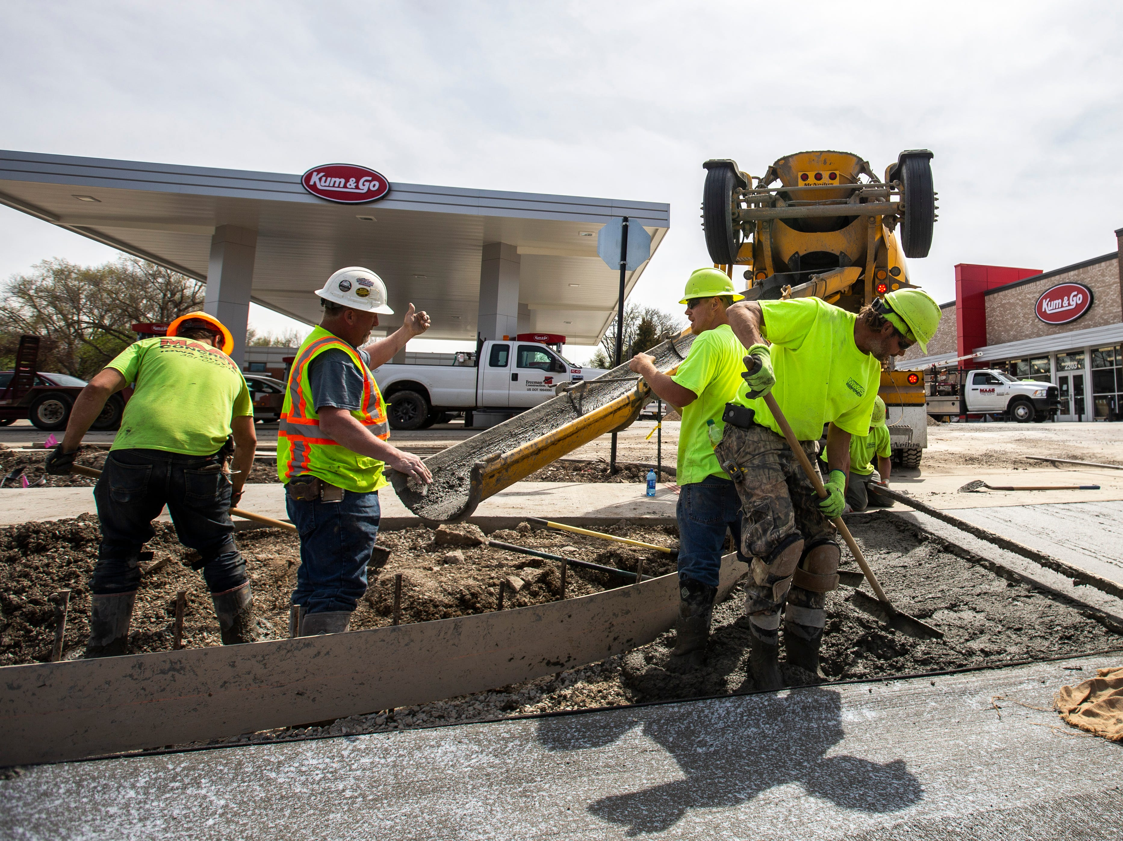 Bud Maas Concrete foreman Steve Conley, second from left, gives instructions while concrete gets poured for an entrance off of Muscatine Ave. while construction nears competition, Tuesday, April 23, 2019, at a new Kum & Go location on the corner of Muscatine and First Avenues on the east side of Iowa City, Iowa.