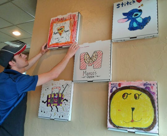General Manager Mo Rashid shown here has made a display of past elementary school pizza box artwork for this wall at Marco's Pizza in North Liberty.