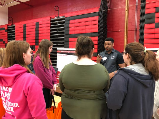 Tyler Ladd, of Corning Community College, speaks with Spencer-Van Etten students during a job fair held recently for juniors and seniors at S-VE High School.