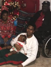"Lonnie ""Lil Lonnie"" Taylor holds his niece while posing for a picture with his sister and father on Christmas Day in 2017."