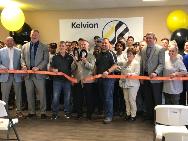 Travis Nichols, chief financial officer for Kelvion US, wields the big scissors at the ribbon-cutting for the industrial HVAC factory Tuesday, April 23, 2019.