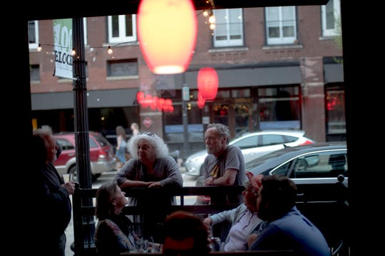 Friends stop to chat with Patti Smith as she dines at Cru Bistro on April 17.