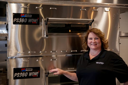 Holly O'Neil, co-owner, poses for a photo in front of the new pizza ovens at Noble Roman's restaurant, Tuesday, April 23, 2019, in Lafayette.