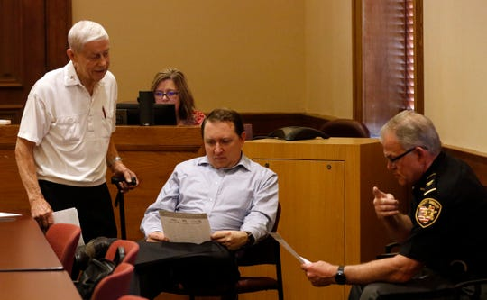 Ray Stemen, left, from Bremen, talks to Fairfield County Clerk of Courts Branden Meyer, center, and Fairfield County Sheriff's Office Chief Deputy Alex Lape after handing them a paper to read during a break in the Fairfield County Commissioner's meeting Tuesday, April 23, 2019, in Lancaster.