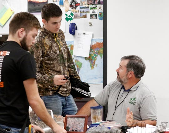 Bryson L'Huillier, center, talks to his agricultural teacher Jeff Tilley Tuesday morning, April 23, 2019, after class at Amanda-Clearcreek High School in Amanda.