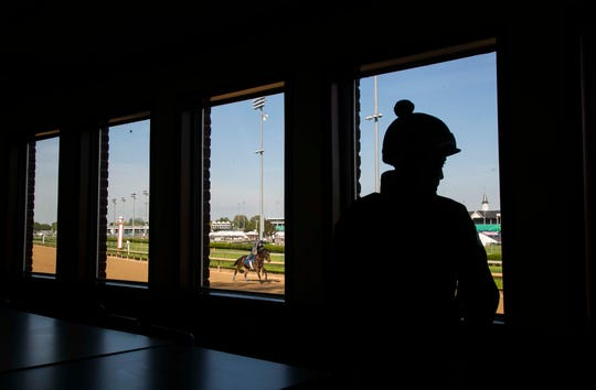 An exercise rider watches from inside the Post Time Kitchen as horses train one morning before Derby Week recently. The dining area offers trackside views. April 20, 2019