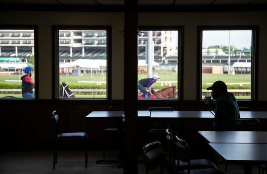 An track worker sips his coffee as horses train nearby along the track at Churchill Downs' backside Post Time Kitchen one morning before Derby Week recently. The small eatery offers breakfast starting at 6 a.m. and lunch until 1:30 pm.  April 20, 2019