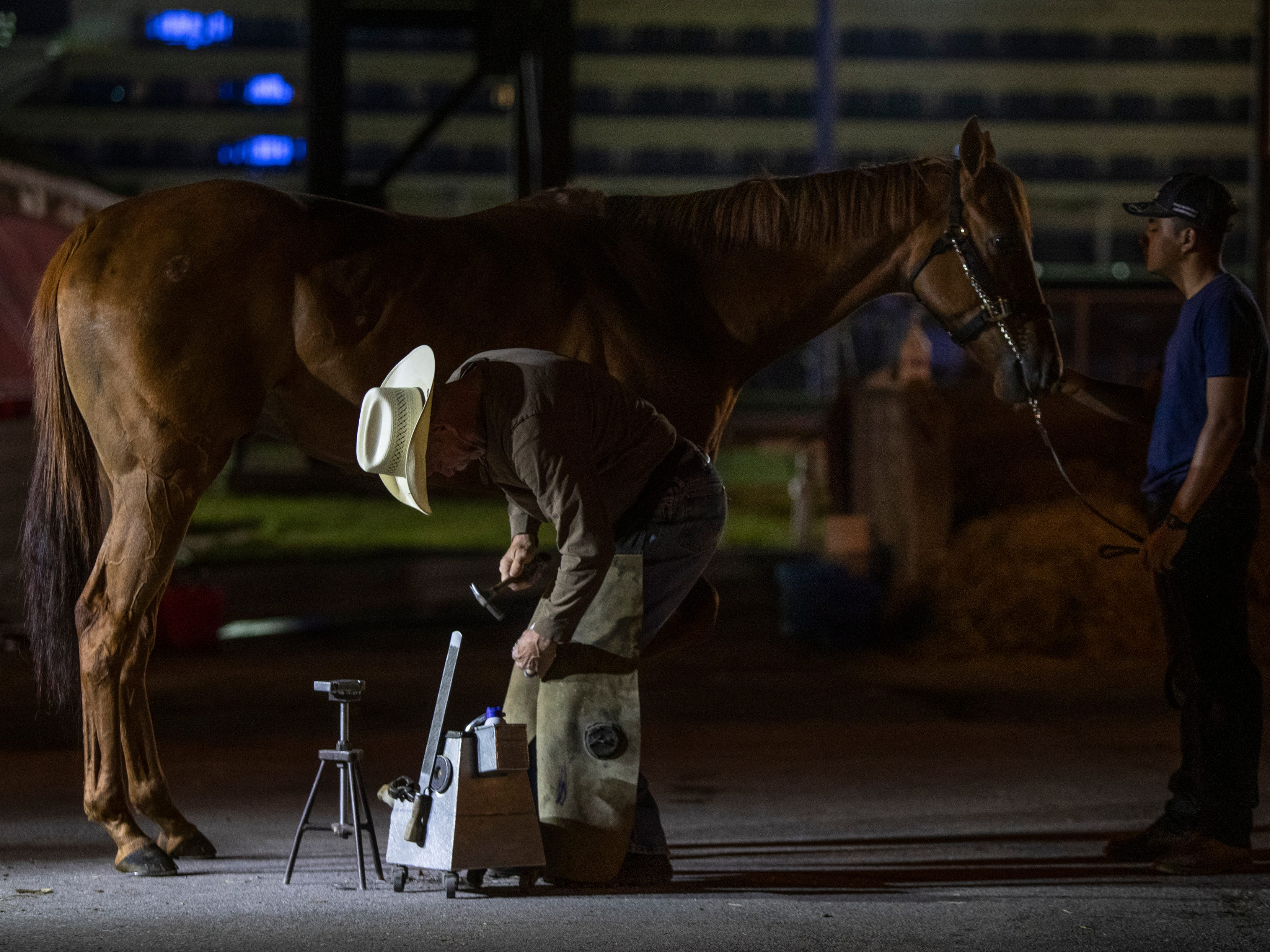 Blacksmith Steve Norman puts a new set of shoes on Carson Can in the early morning at Churchill Downs while being held by Wilner Antonio. Carson Can is trained by Greg Foley. April 23, 2019.
