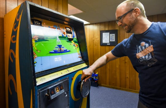 """Ryan Claytor of Holt, an artist and Michigan State University assistant professor in the Department of Art, Art History and Design, demonstrates """"Penny Pitch,"""" Tuesday, April 23, 2019.  It's an electro-mechanical arcade game from the 1970's.  Claytor has a collection of 15 pinball machines in his basement."""