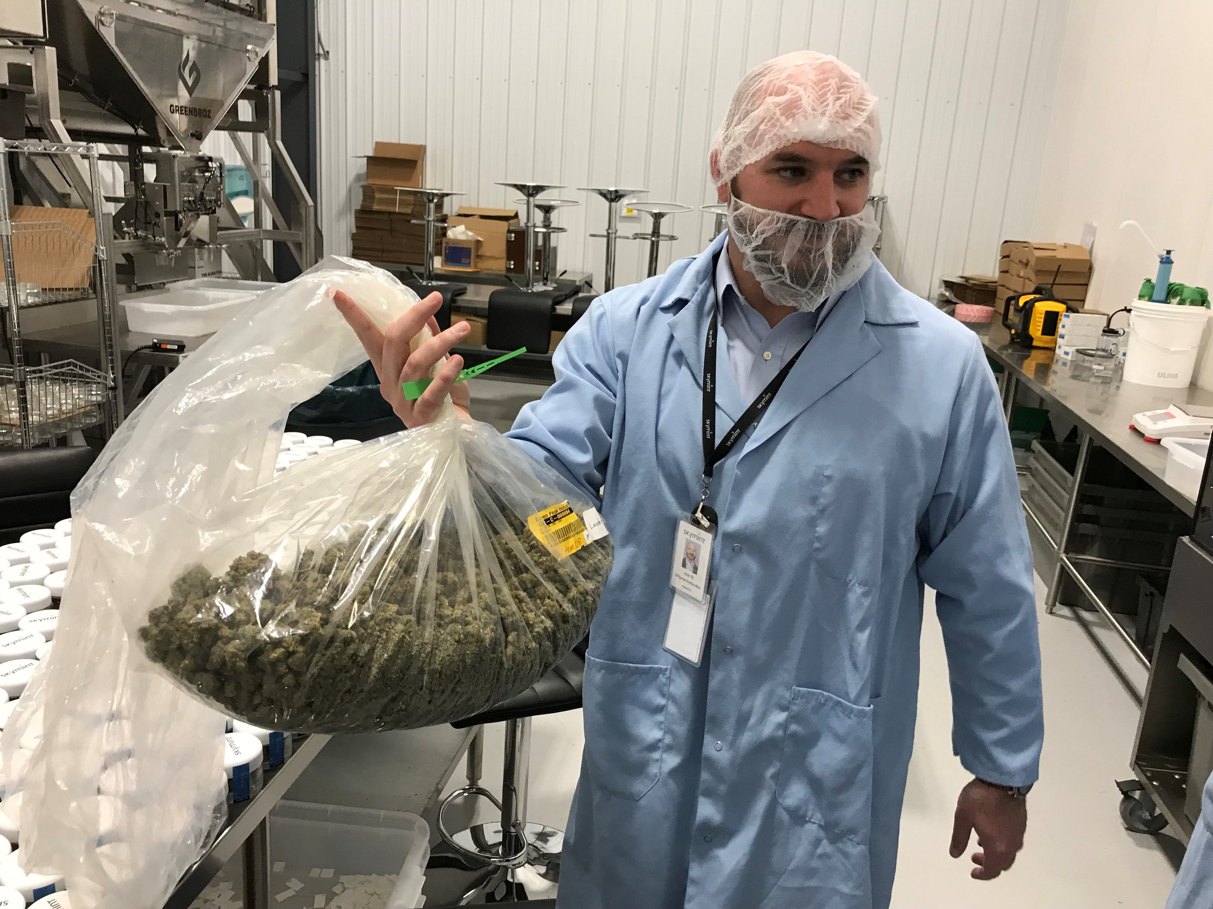 Green Peak Innovations' Joe Neller, executive vice president, shows a bag of marijuana that's grown at its Windsor Township, Michigan facility.