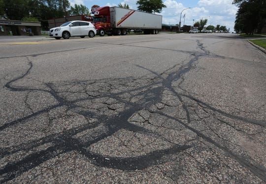 Cars go north on a crack-filled section of North Central Avenue in Marshfield, June 24, 2015, between Harrison and Grant streets.