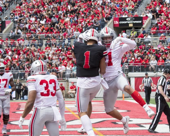 Ohio State quarterback Justin Fields (1) celebrates a touchdown in the spring game with receiver Austin Mack.