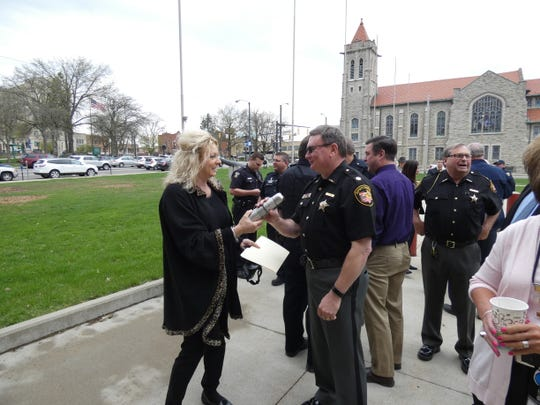 Sherry Branham, associate director of the Richland County Mental Health & Recovery Services, gives Major Joe Masi of the Richland County Sheriff's Office a to-go coffee mug Tuesday during the Honor First Responders ceremony on the Richland County Courthouse lawn.