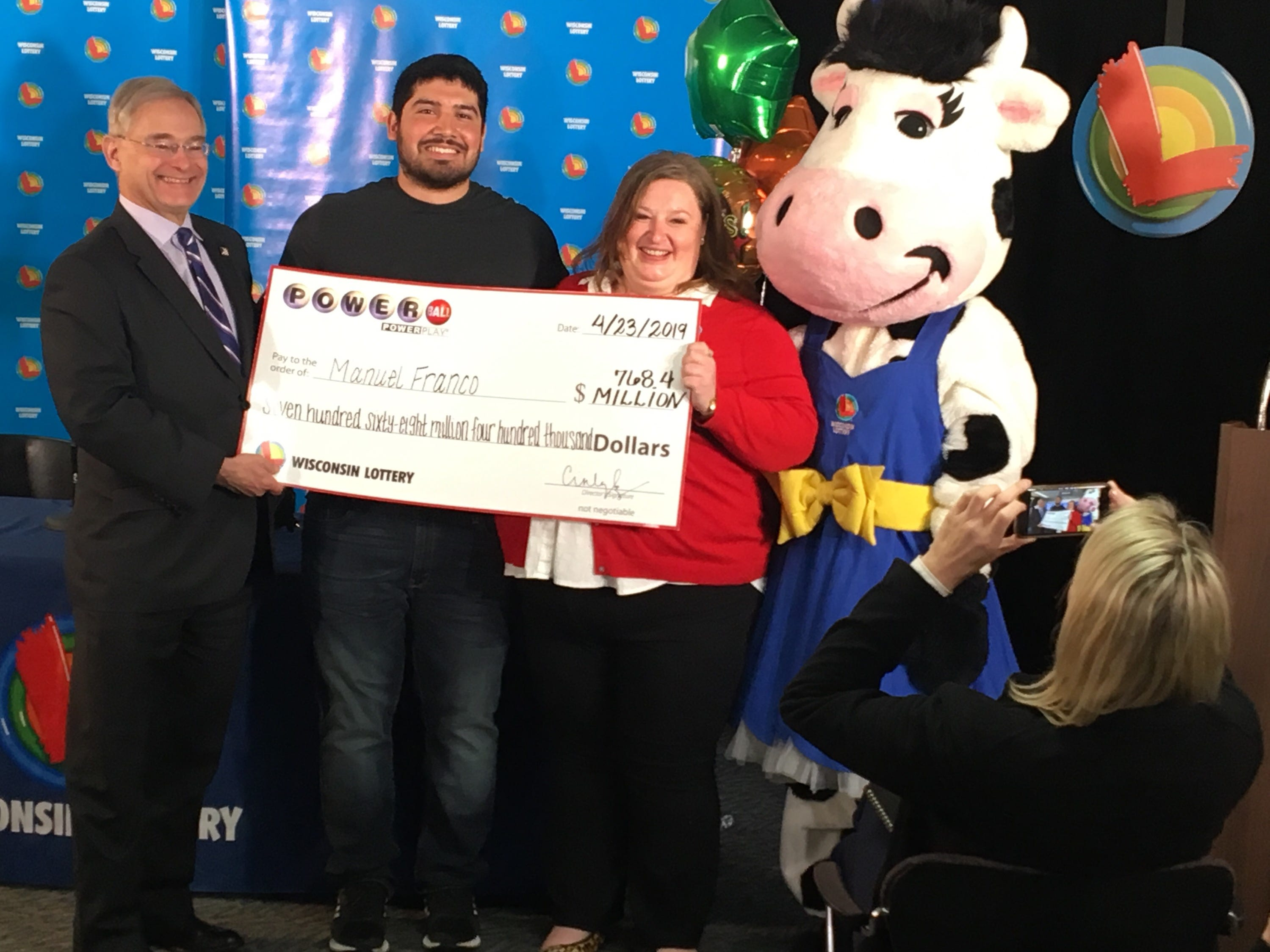 Manuel Franco, 24, of West Allis, is the winner of the $768.4 million Powerball jackpot. Franco was identified early Tuesday afternoon at the state lottery headquarters. With him are Wisconsin Department of Revenue Secretary Peter Barca, Wisconsin Lottery Director Cindy Polzin and Moola, the lottery mascot.