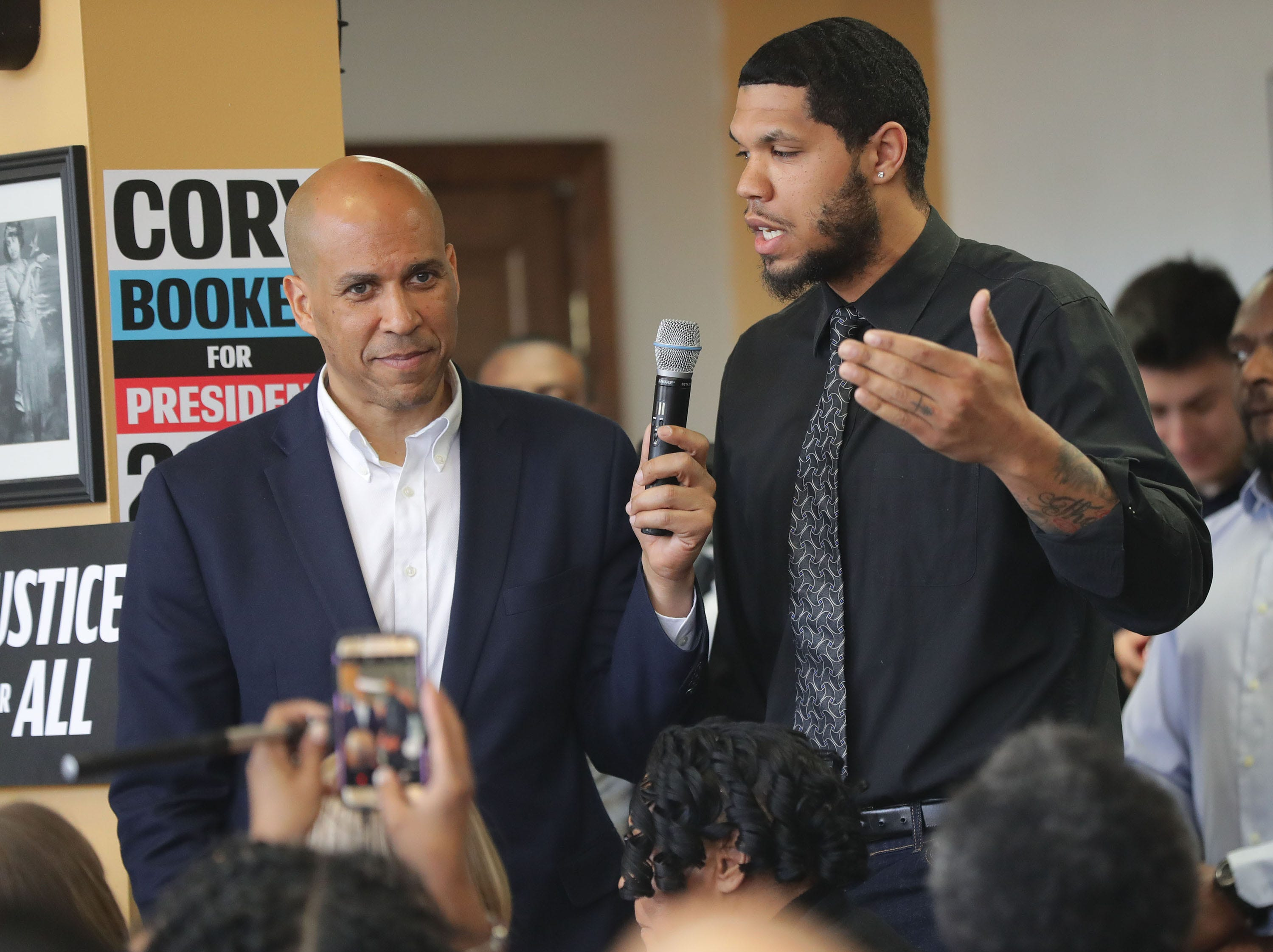U.S. Sen. Cory Booker takes a question from Anthony Hill of Milwaukee. Booker made a campaign stop at Coffee Makes You Black on North Teutonia Avenue in Milwaukee on Tuesday.