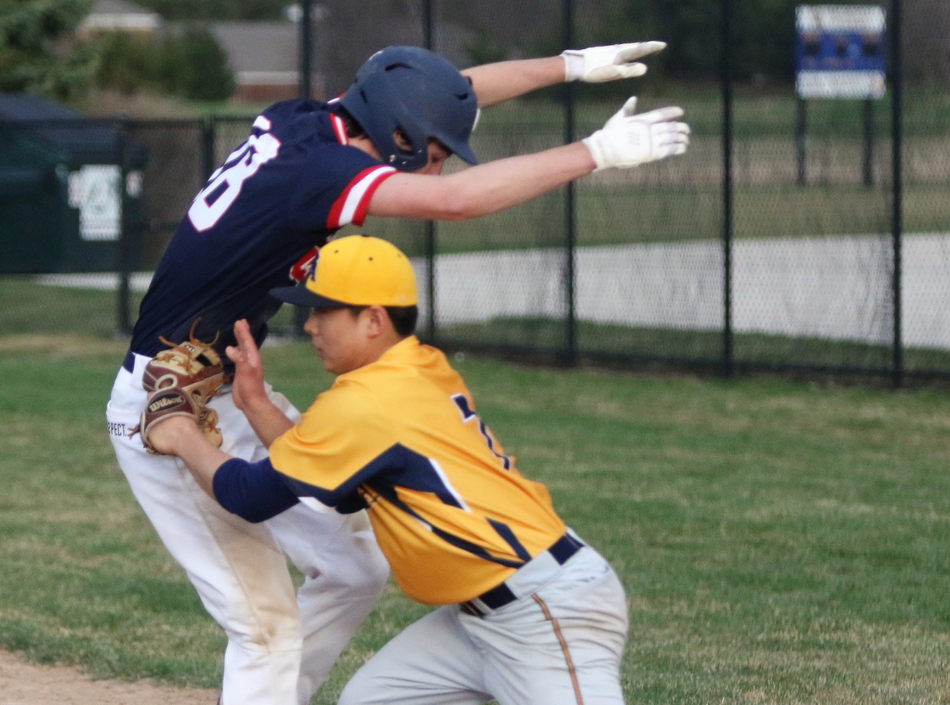 Brookfield Academy pitcher Daniel Kim tags out Brookfield East's Ethan Toone at home plate on April 22, 2019.