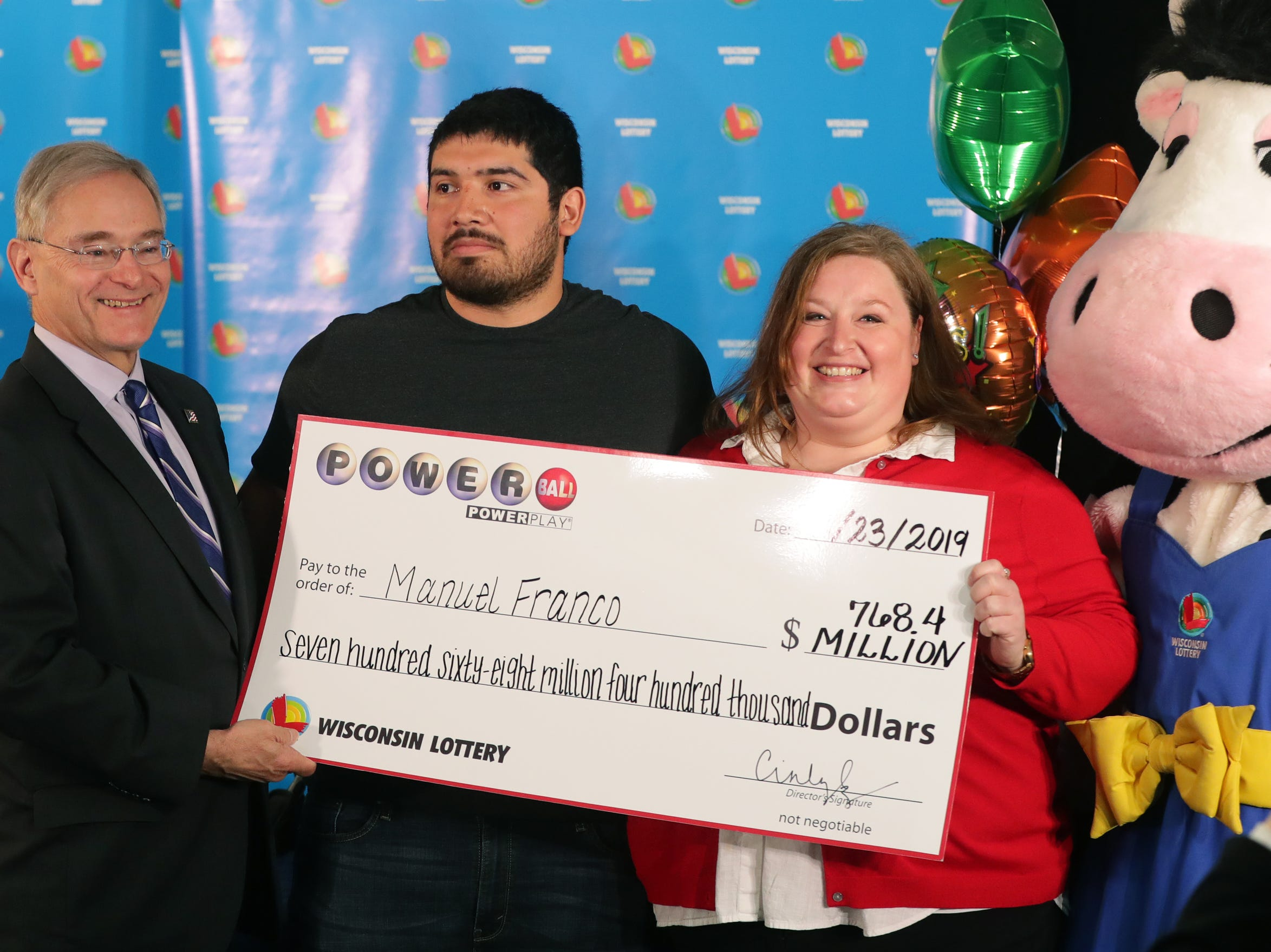 Manuel Franco, 24, second from left, of West Allis is the winner of the $768.4 million Powerball jackpot. Franco was identified early Tuesday afternoon at the state lottery headquarters. He took the lump sum payout of $477 million. With him are Wisconsin Department of Revenue Secretary Peter Barca, Wisconsin Lottery Director Cindy Polzin and Moola, the lottery mascot.