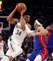 Bucks forward Giannis Antetokounmpo  is fouled by Pistons guard Bruce Brown.