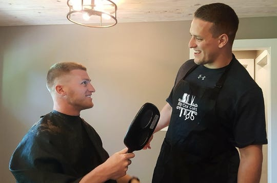 Chandler Cox (right) checks his work after cutting the hair of Griffin King (left) in his house on April 17, 2019, in Auburn, Ala.