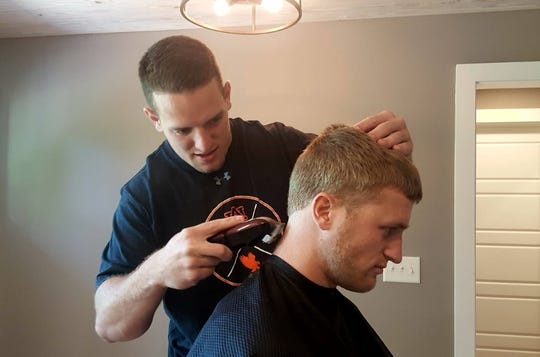 Chandler Cox (left) cuts the hair of Griffin King (right) in his house on April 17, 2019, in Auburn, Ala.